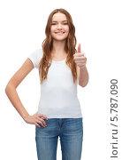 """Купить «Улыбающаяся девушка в белой футболке и джинсах показывает жест """"все хорошо""""», фото № 5787090, снято 26 февраля 2014 г. (c) Syda Productions / Фотобанк Лори"""