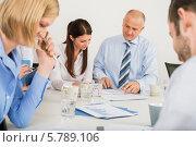 Купить «Деловая команда изучает документы за столом в переговорной комнате», фото № 5789106, снято 2 марта 2014 г. (c) CandyBox Images / Фотобанк Лори