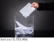 Купить «рука бросает бюллетень в прозрачную урну для голосования», фото № 5793466, снято 5 января 2014 г. (c) Андрей Попов / Фотобанк Лори