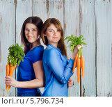 Две улыбающиеся девушки держат в руках пучки моркови. Стоковое фото, фотограф Tatjana Baibakova / Фотобанк Лори