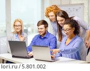 Молодой творческий коллектив. Коллеги в офисе что-то обсуждают, глядя на краны ноутбуков. Стоковое фото, фотограф Syda Productions / Фотобанк Лори