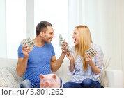 Молодая семья радуется накопленным деньгам. Свинья-копилка на столе. Стоковое фото, фотограф Syda Productions / Фотобанк Лори