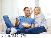 Купить «Молодые мужчина и женщина дома с миской покорна перед телевизором», фото № 5801278, снято 9 февраля 2014 г. (c) Syda Productions / Фотобанк Лори