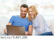 Купить «Счастливая молодая пара смотрит на экран ноутбука, сидя дома на диване», фото № 5801290, снято 9 февраля 2014 г. (c) Syda Productions / Фотобанк Лори