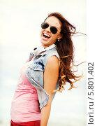 Купить «Девушка с развевающимися длинными волосами и в темных очках громко смеется», фото № 5801402, снято 20 июля 2013 г. (c) Syda Productions / Фотобанк Лори