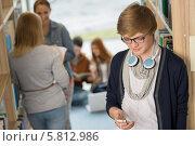 Студент пишет сообщение на мобильном телефоне стоя в библиотеке. Стоковое фото, фотограф CandyBox Images / Фотобанк Лори