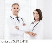 Купить «Два врача, мужчина и женщина, стоя, скрестив руки, в клинике», фото № 5815418, снято 6 июля 2013 г. (c) Syda Productions / Фотобанк Лори