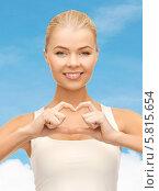Купить «Улыбающаяся девушка сложила сердце с помощью рук», фото № 5815654, снято 23 марта 2013 г. (c) Syda Productions / Фотобанк Лори