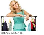 Купить «Блондинка стоит возле вешалки с одеждой», фото № 5829446, снято 15 апреля 2014 г. (c) Andrejs Pidjass / Фотобанк Лори