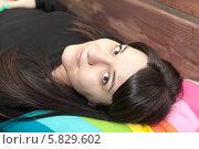 Симпатичная девушка с темными волосами лежит на спине, смотрит в камеру. Стоковое фото, фотограф Кекяляйнен Андрей / Фотобанк Лори