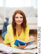 Купить «Симпатичная студентка в желтой блузке готовится к экзаменам дома, лежа на полу с книгами и учебниками», фото № 5830262, снято 19 марта 2014 г. (c) Syda Productions / Фотобанк Лори