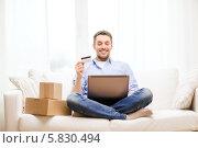 Купить «Мужчина сидя дома на диване заказывает товары через интернет», фото № 5830494, снято 15 марта 2014 г. (c) Syda Productions / Фотобанк Лори