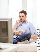 Молодой человек ест попкорн и смотрит дома телевизор, сидя на диване дома. Стоковое фото, фотограф Syda Productions / Фотобанк Лори