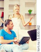 Купить «Семейная ссора. Девушка ругается на мужчину, который читает новости на экране планшетного компьютера», фото № 5830562, снято 4 августа 2012 г. (c) Syda Productions / Фотобанк Лори