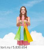 Купить «Юная девушка в розовом платье показывает пакеты с покупками на фоне голубого неба», фото № 5830654, снято 26 февраля 2014 г. (c) Syda Productions / Фотобанк Лори