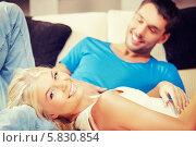Купить «Молодая счастливая пара отдыхает дома», фото № 5830854, снято 4 августа 2012 г. (c) Syda Productions / Фотобанк Лори