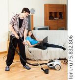 Купить «Мужчина пылесосит пол, а женщина лежит на диване с ноутбуком», фото № 5832806, снято 12 марта 2014 г. (c) Яков Филимонов / Фотобанк Лори