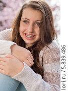 Купить «Девушка с брекетами на зубах сидит, обняв колени в парке», фото № 5839486, снято 4 апреля 2014 г. (c) CandyBox Images / Фотобанк Лори