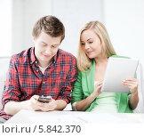 Купить «Девушка с документами в руках смотрит на молодого человека, читающего сто-то на смартфоне», фото № 5842370, снято 16 июня 2013 г. (c) Syda Productions / Фотобанк Лори