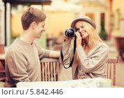 Девушка фотографирует своего молодого человека во время свидания за столиком уличного кафе. Стоковое фото, фотограф Syda Productions / Фотобанк Лори