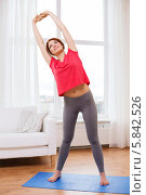 Купить «Занятие спортом в домашних условиях. Девушка делает наклоны, стоя на гимнастическом коврике», фото № 5842526, снято 19 марта 2014 г. (c) Syda Productions / Фотобанк Лори
