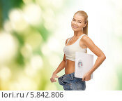 Купить «Стройная девушка в больших джинсах и с весами в руках. Концепция похудения», фото № 5842806, снято 23 марта 2013 г. (c) Syda Productions / Фотобанк Лори