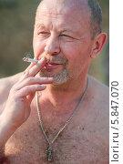 Купить «Мужчина с голым торсом курит сигарету», эксклюзивное фото № 5847070, снято 20 апреля 2014 г. (c) Игорь Низов / Фотобанк Лори