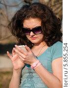 Молодая женщина набирает номер телефона на улице. Стоковое фото, фотограф Игорь Низов / Фотобанк Лори