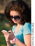 Молодая женщина нажимает кнопки телефона на прогулке. Стоковое фото, фотограф Игорь Низов / Фотобанк Лори