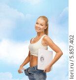 Купить «Девушка с напольными весами оттянула пояс джинсов и улыбается, радуясь снижению веса», фото № 5857402, снято 23 марта 2013 г. (c) Syda Productions / Фотобанк Лори