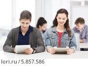 Два студента - молодой человек и девушка смотрят на экраны планшетных компьютеров, сидя на лекции в аудитории. Стоковое фото, фотограф Syda Productions / Фотобанк Лори