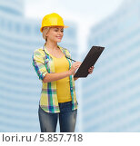 Купить «Улыбающаяся женщина в желтой каске и в рабочей одежде стоит с клипбордом в руках на фоне современного здания», фото № 5857718, снято 16 февраля 2014 г. (c) Syda Productions / Фотобанк Лори