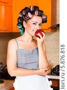 Женщина в бигуди ести яблоко на кухне. Стоковое фото, фотограф Андрей Затулло / Фотобанк Лори