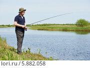 Купить «Рыбак ловит рыбу на удочку, стоя на берегу летнего водоема», фото № 5882058, снято 26 апреля 2014 г. (c) Дмитрий Калиновский / Фотобанк Лори