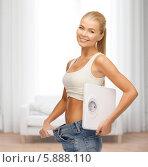 Купить «Улыбающаяся девушка в больших джинсах держит напольные весы в руках», фото № 5888110, снято 23 марта 2013 г. (c) Syda Productions / Фотобанк Лори