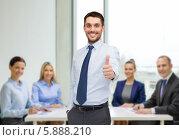 Купить «Энергичный бизнесмен поднял большой палец руки вверх, стоя в офисе», фото № 5888210, снято 15 марта 2014 г. (c) Syda Productions / Фотобанк Лори