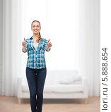 Купить «Девушка в клетчатой рубашке и в джинсах стоит в комнате и показывает жест одобрения обеими руками», фото № 5888654, снято 12 февраля 2014 г. (c) Syda Productions / Фотобанк Лори