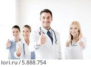 Купить «Молодой врач со своими коллегами показывает жест одобрения - большой палец руки поднят вверх», фото № 5888754, снято 18 мая 2013 г. (c) Syda Productions / Фотобанк Лори