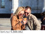 Портрет молодой счастливой пары с мобильным телефоном на улице. Стоковое фото, фотограф Яна Королёва / Фотобанк Лори