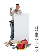 Купить «плотник держит пустой баннер и указывает на телефон», фото № 5889522, снято 25 ноября 2009 г. (c) Phovoir Images / Фотобанк Лори