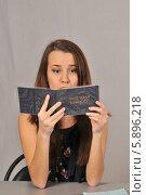 Девушка-студентка, сидя за партой, глядит с недоумением в зачётку. Стоковое фото, фотограф Малышев Андрей / Фотобанк Лори