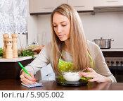 Купить «Молодая домохозяйка на кухне взвешивает на весах чашку с творогом», фото № 5905002, снято 28 февраля 2014 г. (c) Яков Филимонов / Фотобанк Лори