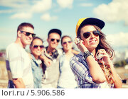 Купить «Девушка в солнцезащитных очках, бейсболке и с наушниками стоит рядом со своими друзьями на улице», фото № 5906586, снято 20 июля 2013 г. (c) Syda Productions / Фотобанк Лори
