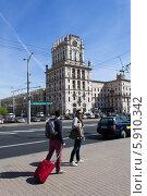 Путешественники с красным чемоданом и рюкзаком на привокзальной площади (2014 год). Редакционное фото, фотограф Евгений Самсонов / Фотобанк Лори