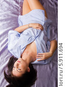 Девушка лежит на спине на кровати. Стоковое фото, фотограф Евгений Леонов / Фотобанк Лори