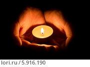 Горящая чайная свеча в женских ладонях на чёрном фоне. Стоковое фото, фотограф Anton Kozyrev / Фотобанк Лори