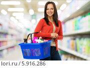 Купить «Улыбающаяся девушка с корзиной бытовой химии в магазине», фото № 5916286, снято 29 апреля 2014 г. (c) Andrejs Pidjass / Фотобанк Лори