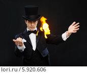 Купить «Фокусник в черной шляпе на черном фоне показывает фокус с огнем», фото № 5920606, снято 12 сентября 2013 г. (c) Syda Productions / Фотобанк Лори