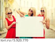 Купить «Три счастливые подруги показывают палцами на пустой баннер, который держат перед собой», фото № 5920770, снято 8 сентября 2013 г. (c) Syda Productions / Фотобанк Лори