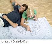 Купить «Счастливая пара изучает план квартиры, лежа на полу», фото № 5924418, снято 28 мая 2018 г. (c) BE&W Photo / Фотобанк Лори